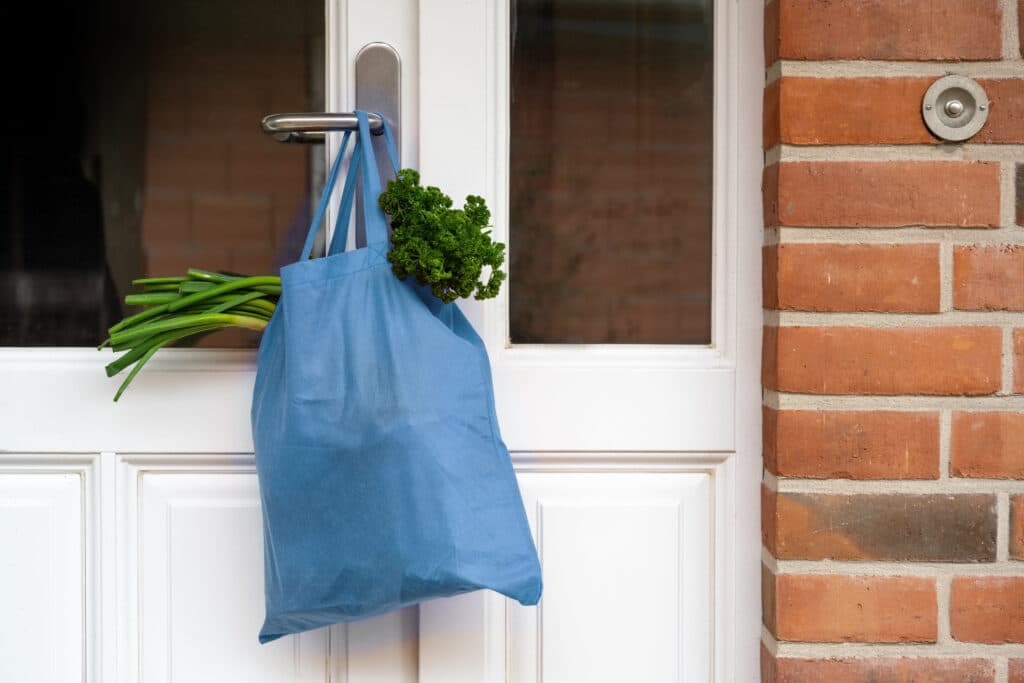 blue_shopping_bag_with_groceries_hanging_from_door_handle